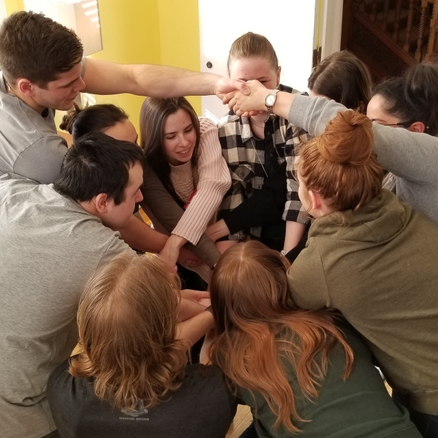 Participants create a human knot for a team building game.